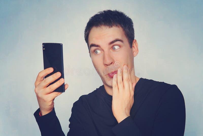 英俊的年轻人特写镜头画象由什么冲击了惊奇的,开放嘴和眼睛,他在他的手机看见,在蓝色backgrou 免版税库存照片