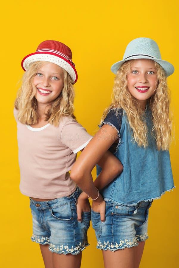 英俊的年轻人画象孪生夏天帽子的女孩,摆在黄色背景 免版税库存图片