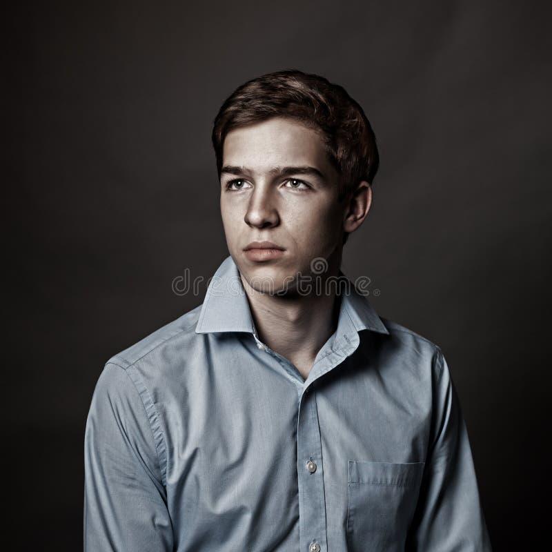 英俊的年轻人画象灰色背景的, 免版税库存图片