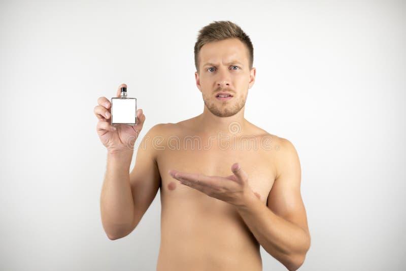 英俊的年轻人的图象有拿着parfume和指向白色被隔绝的背景的赤裸躯干的在一只手上 免版税库存照片