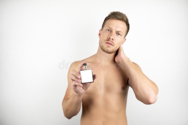 英俊的年轻人的图象有拿着parfume白色被隔绝的背景的赤裸躯干的 库存照片