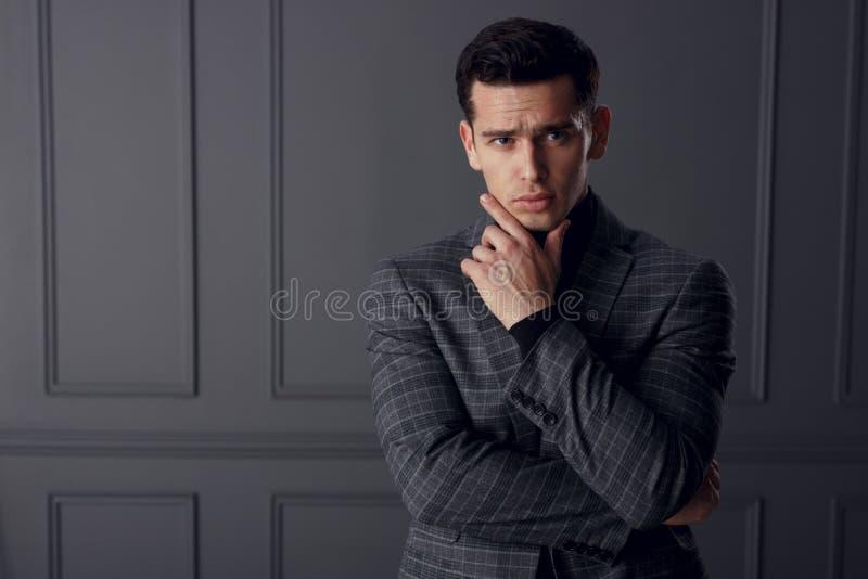 英俊的年轻人穿戴画象在摆在商人的位置的格子花呢披肩夹克的,在灰色背景 免版税库存照片