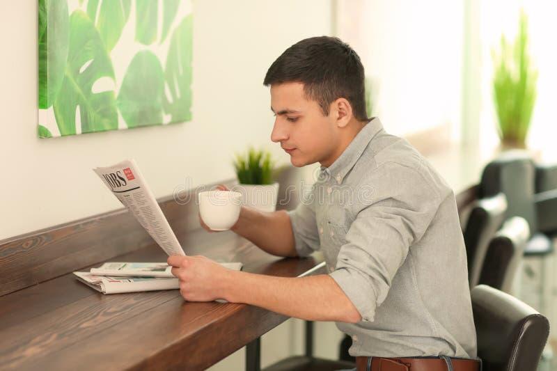 英俊的年轻人读书报纸,当喝在咖啡馆时的咖啡 免版税库存图片