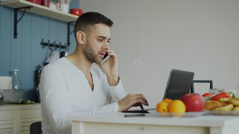 英俊的年轻人谈的电话和使用坐在厨房里在早餐以后的便携式计算机早晨 免版税库存照片