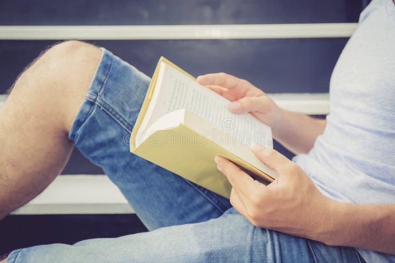英俊的年轻便衣阅读书的企业亚裔人与休闲在客厅 免版税库存照片