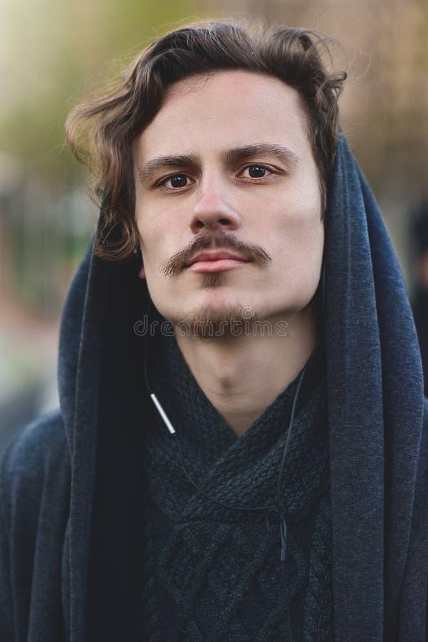 英俊的年轻卷曲戴头巾人考虑某事,调查照相机 reeady战斗 免版税库存照片