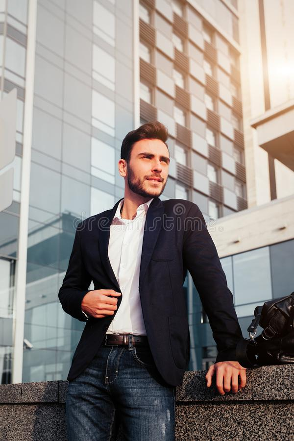 英俊的年轻商人与胡子和在街道上的一个西装身分以办公室为背景 图库摄影
