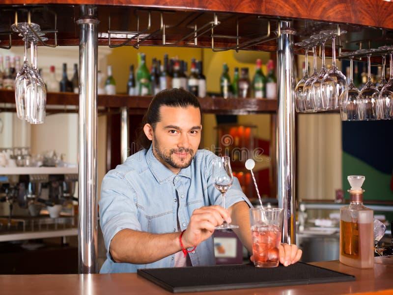 英俊的年轻微笑的barista人提供的鸡尾酒饮料 免版税库存照片