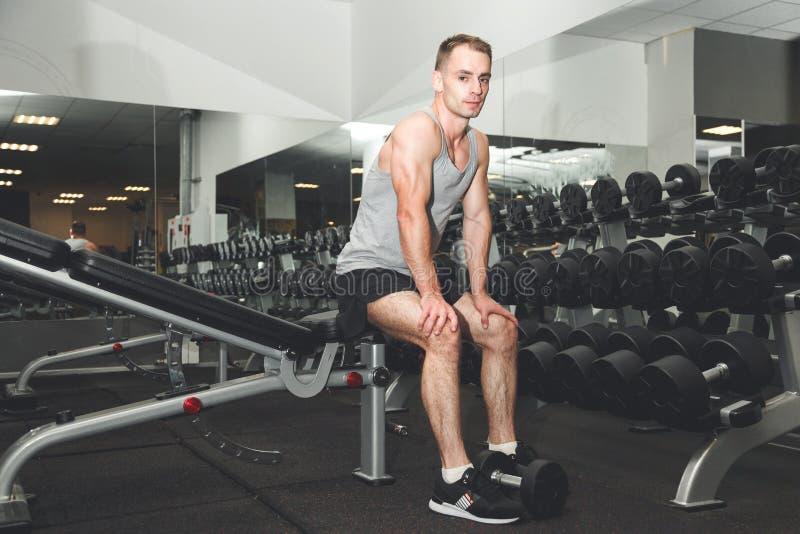 英俊的年轻拉丁人佩带的手套和坐在健身房的一条长凳 库存照片