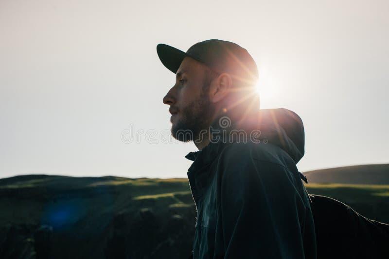 英俊的年轻旅行家画象日落的 免版税图库摄影