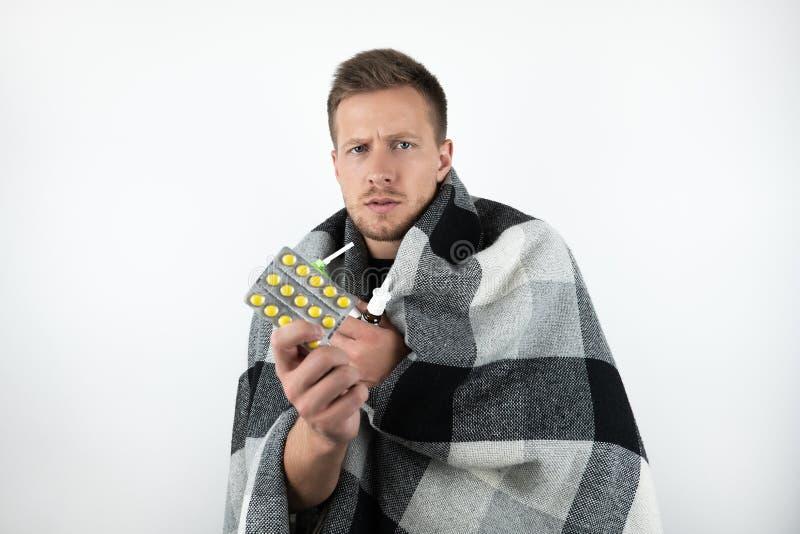 英俊的年轻病的人包裹了方格的格子花呢披肩拿着在被隔绝的白色背景的药片 库存照片
