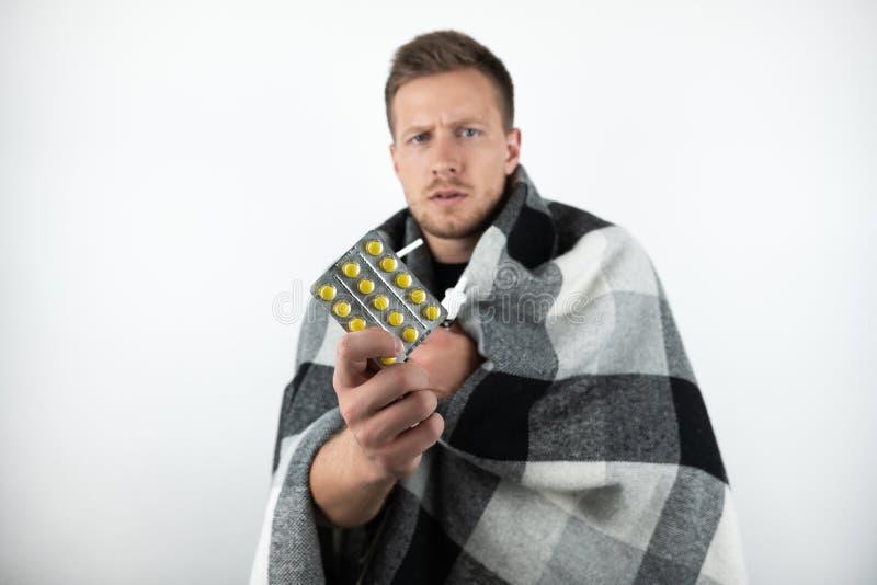 英俊的年轻病的人包裹了方格的格子花呢披肩拿着药片和鼻孔喷射在被隔绝的白色背景 库存图片
