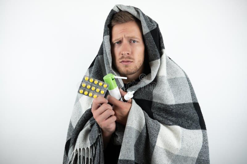 英俊的年轻病的人包裹了方格的格子花呢披肩拿着药片,并且鼻孔喷射在被隔绝的白色背景看怜悯 库存照片