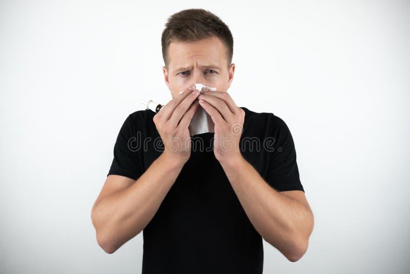 英俊的年轻病的人吹他的在被隔绝的白色背景的鼻子 库存图片