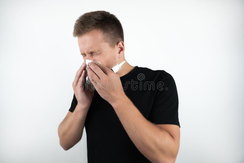 英俊的年轻病的人吹他的鼻子并且拿着在被隔绝的白色背景的鼻孔喷射 免版税库存图片
