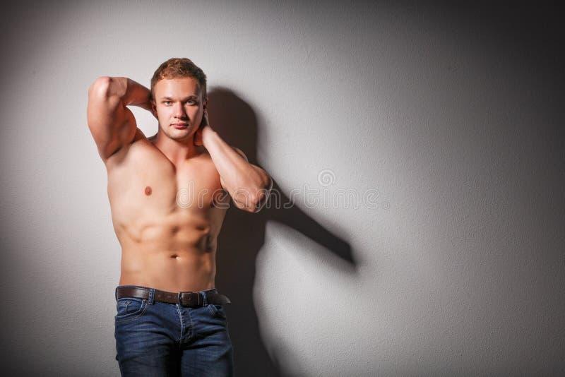 英俊的年轻肌肉赤裸上身的年轻人身分 免版税库存图片