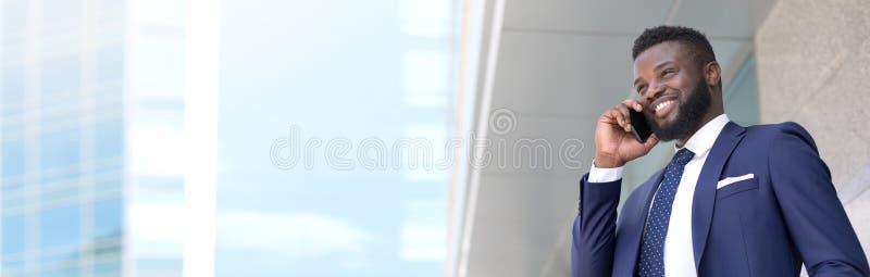 英俊的年轻非洲商人谈话与手机的一个客户外面与拷贝空间 免版税库存图片