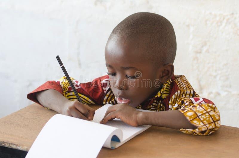 英俊的年轻非洲男孩文字和学会在学校Buildi 免版税库存照片