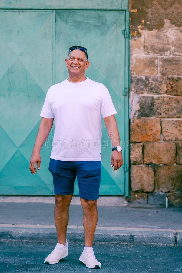 英俊的年迈的商人画象在度假在海附近的 库存照片