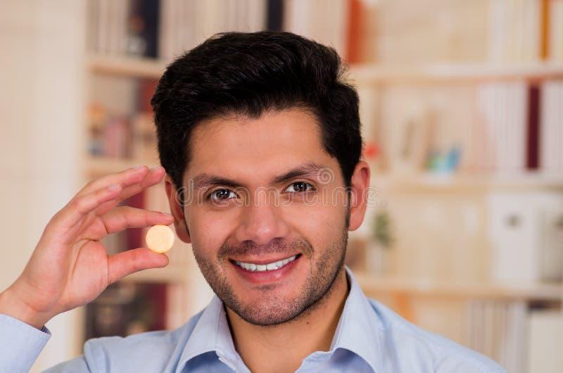 英俊的微笑的人在他的手上的拿着一种药片冒泡片剂 免版税库存照片