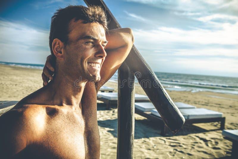 英俊的微笑的人室外在海滩在海 免版税图库摄影