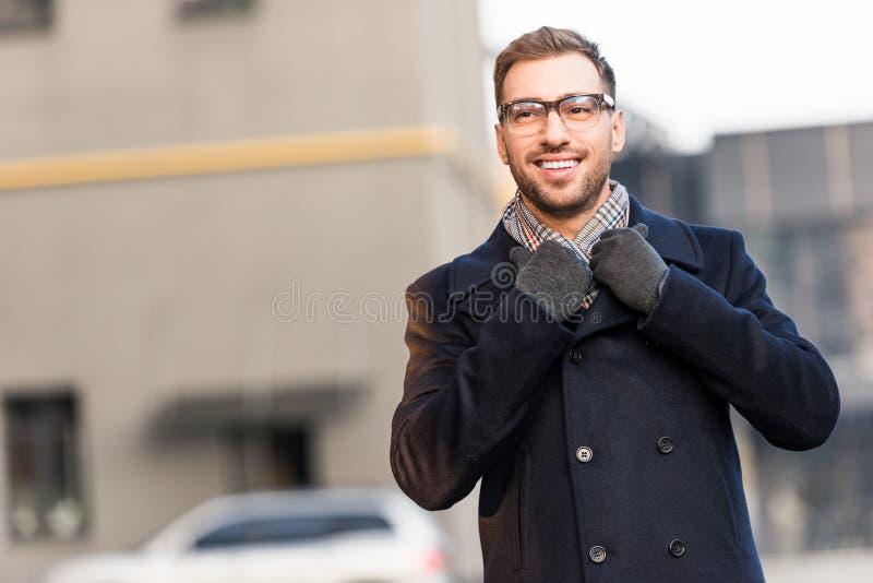 英俊的微笑的人藏品外套衣领 免版税库存图片