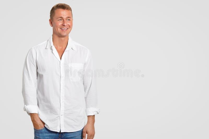 英俊的微笑的年轻商人室内射击高兴他的成功,穿戴在典雅的白色衬衣,反对白色backg的立场 库存图片