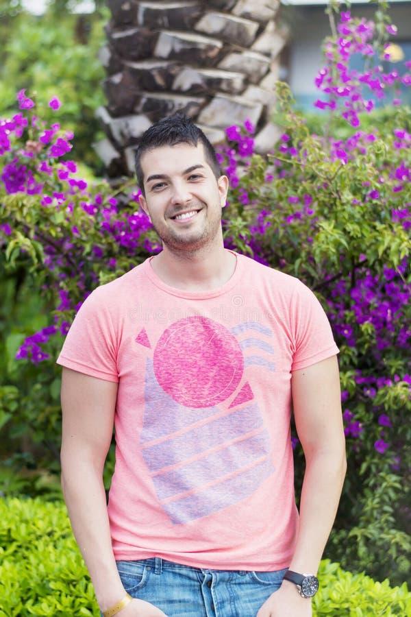 英俊的微笑的有胡子的人在一个热带庭院里 图库摄影