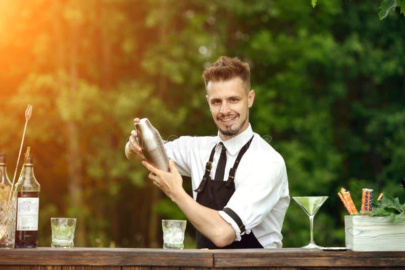 英俊的微笑的男服务员震动的和混合的鸡尾酒户外,加州 免版税库存照片