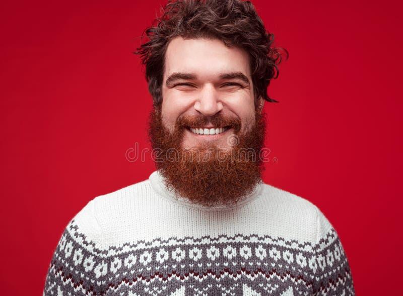 英俊的快乐的人不剃须看对在红色背景的照相机 库存照片