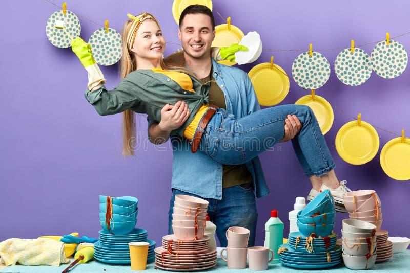 英俊的快乐的人举的女朋友在厨房里 免版税图库摄影