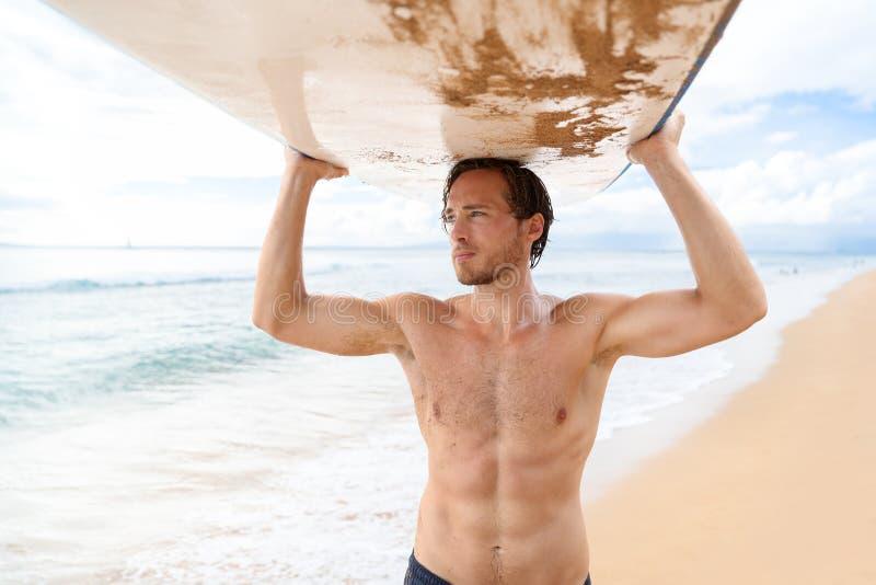 英俊的性感的冲浪者人运载的冲浪板 库存照片