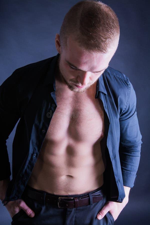英俊的性感的运动的年轻人演播室画象  有穿黑衬衣的赤裸躯干的肌肉人 免版税库存照片