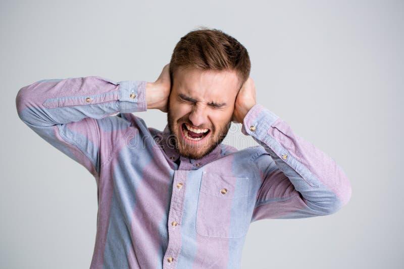 英俊的恼怒的有胡子的人用人工和呼喊关闭了耳朵 库存图片