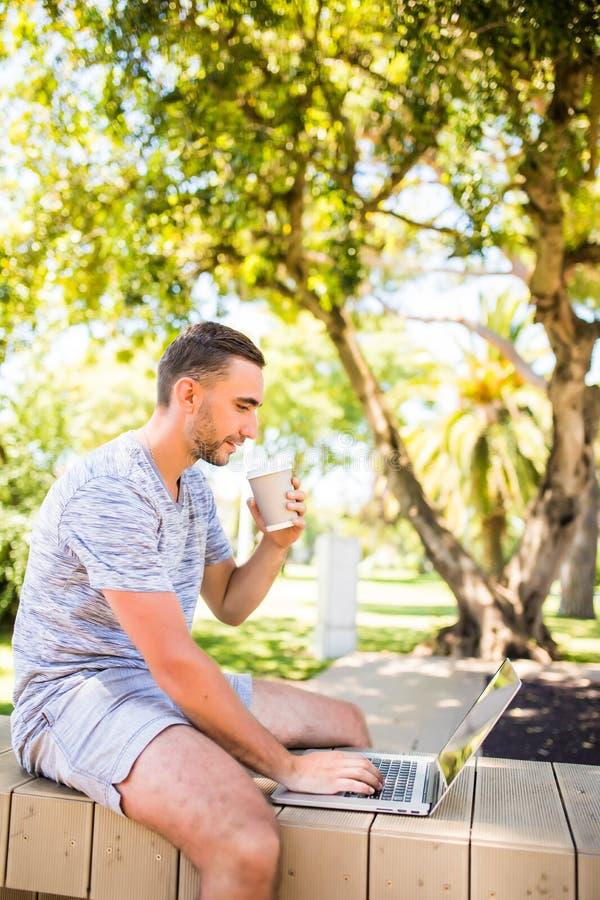 英俊的愉快的人户外在使用手提电脑饮用的咖啡的公园 库存照片