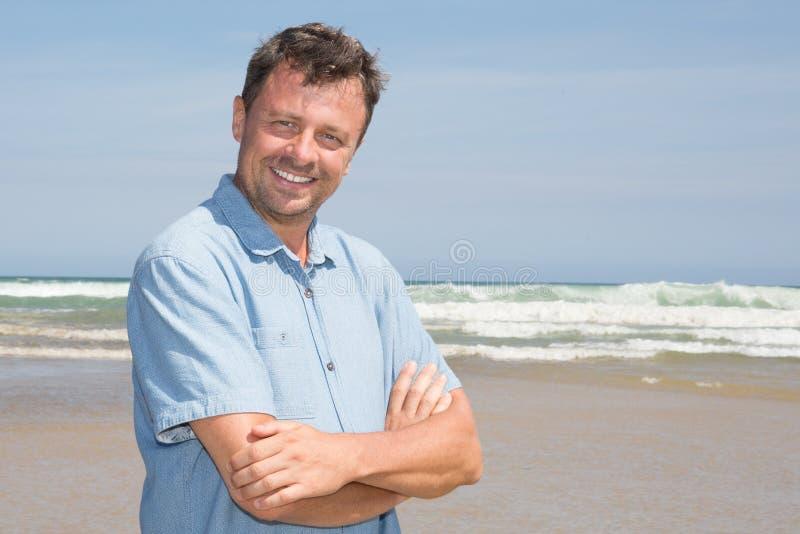 英俊的愉快的摆在海滩海背景的人式样佩带的蓝色衣裳 免版税库存图片