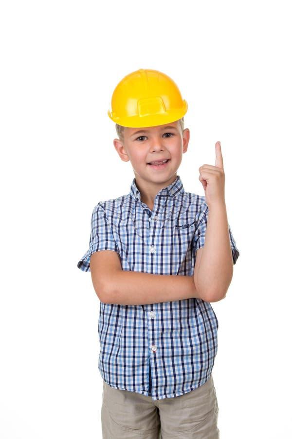 英俊的愉快的未来建造者在蓝色checkred衬衣灰色牛仔裤和黄色盔甲穿戴了,打手势在白色背景 库存照片