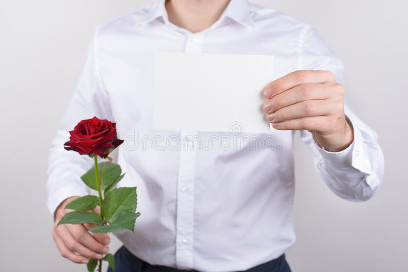 英俊的愉快的迷人的快乐的高兴的人播种的特写镜头照片画象在手上的拿着小明信片显示对您照相机 免版税图库摄影