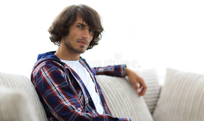 英俊的成功的人坐长沙发 库存照片