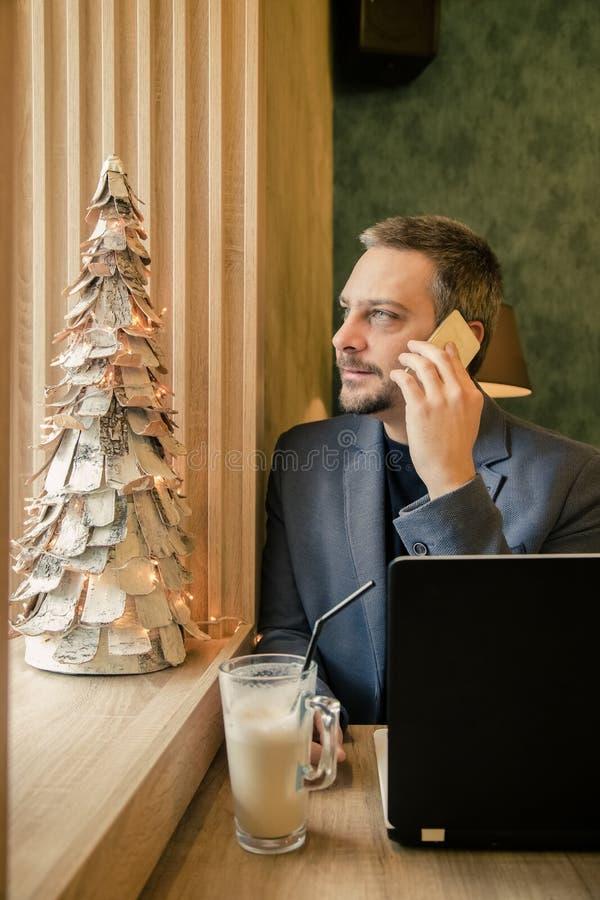 英俊的成功的商人谈话在手机,使用l 免版税库存图片