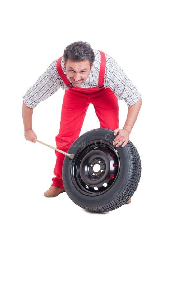 英俊的技工改变的轮胎 免版税库存图片