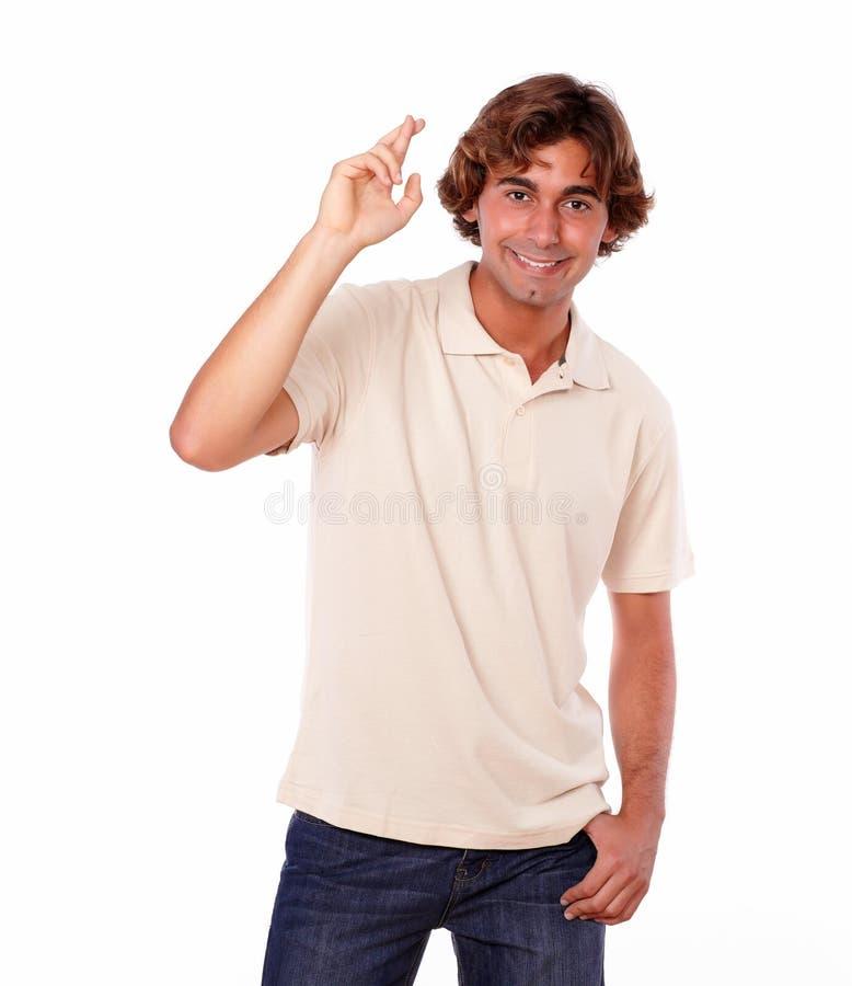 英俊的拉丁年轻人横穿手指 免版税库存图片