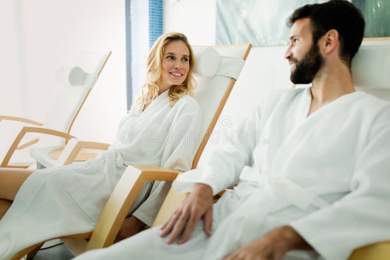 英俊的放松在温泉的男人和美丽的妇女 免版税库存图片