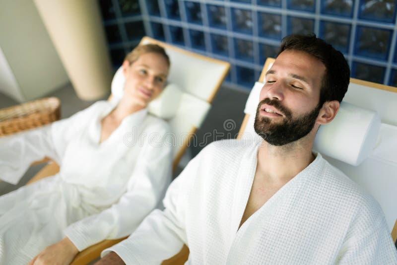 英俊的放松在温泉的男人和美丽的妇女 库存图片