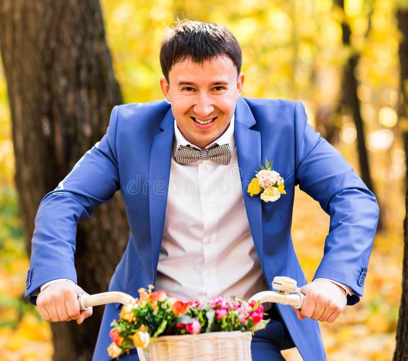 英俊的新郎和葡萄酒骑自行车与在秋天风景背景的花 库存图片