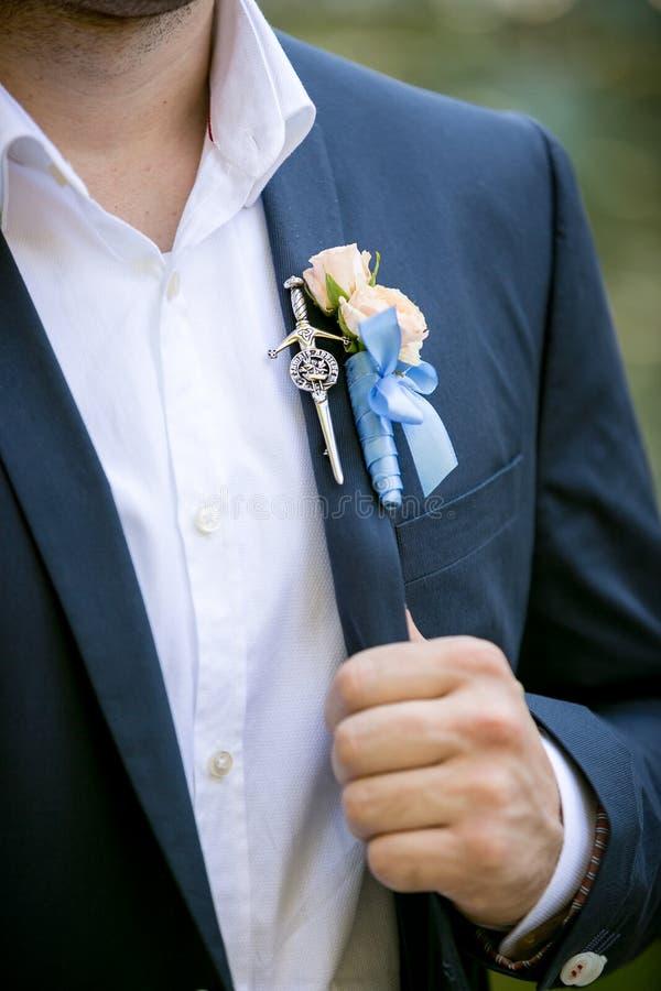 英俊的新郎照片佩带的钮扣眼上插的花的 库存图片