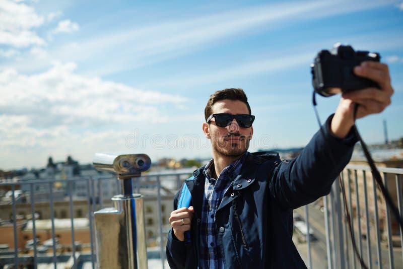 英俊的旅游采取的Selfie有城市视图 库存照片