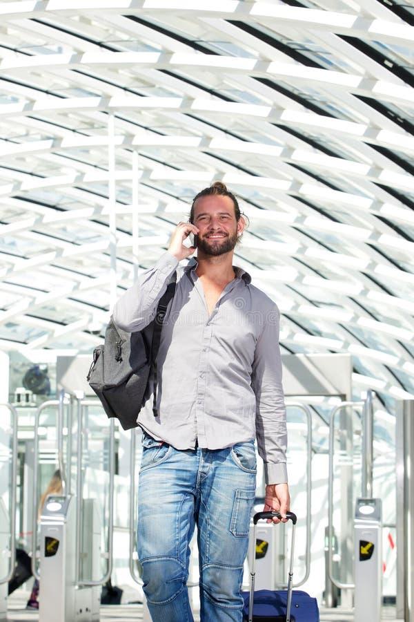 英俊的旅行人谈话在有行李的电话 免版税库存照片