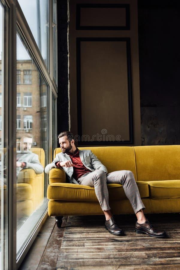 英俊的时兴的人坐黄色沙发和看 免版税库存图片