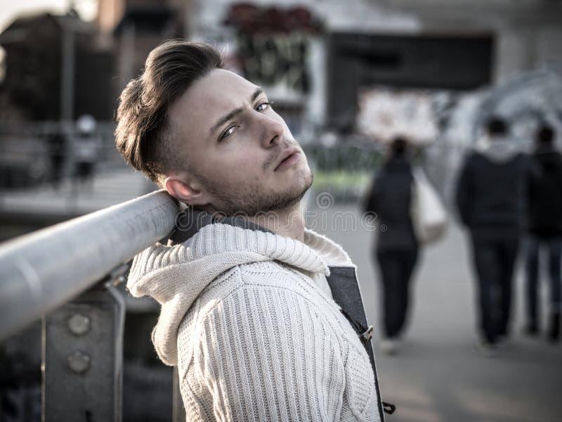 英俊的时髦年轻人,站立在一条边路在城市 免版税库存照片